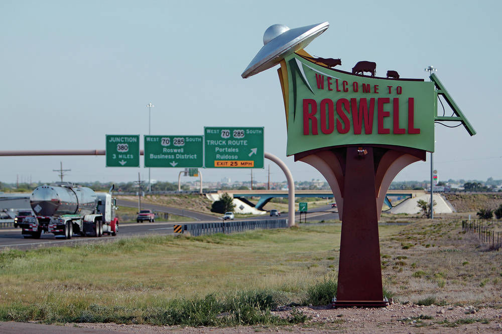 """Welcome to Roswell"" sign with UFOs decorating it"