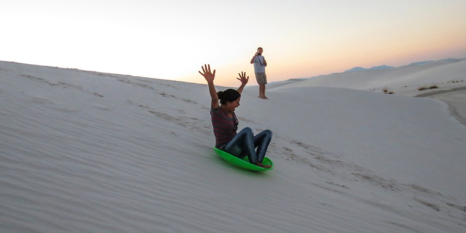 Woman riding a round sled down a sand dune at White Sands National Park in New Mexico