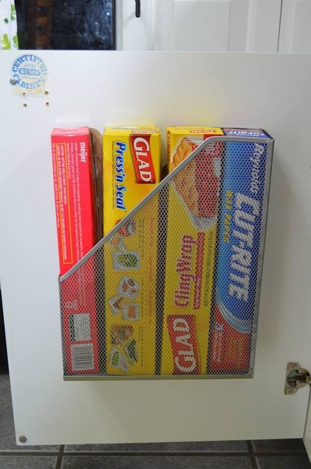 Hang a magazine holder from your cabinet door for plastic wrap and tin foil.