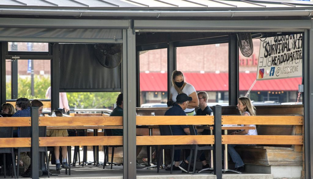 Enjoying a meal on an outdoor patio is a great way to sample new cuisine while responsibly traveling.