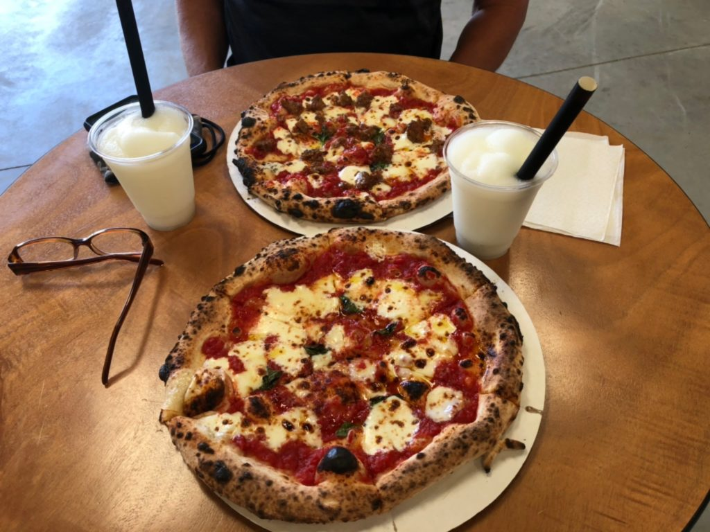 Two delicious wood-fired pizzas sit on a table at Broken Spoke Winery.