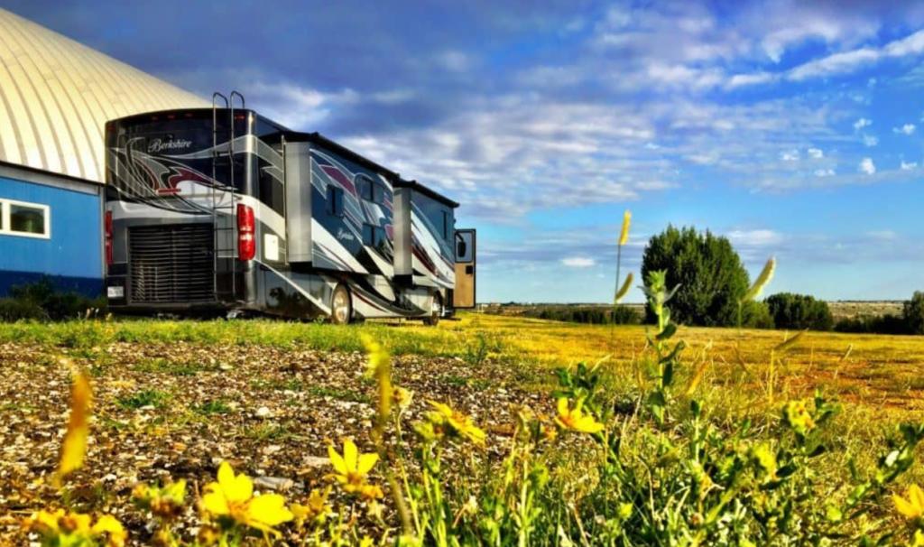 An RV sits beside a barn on a farm