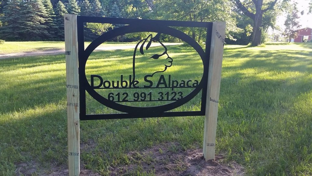 A sign for the Double S Alpaca Farm sits at the front of the property.