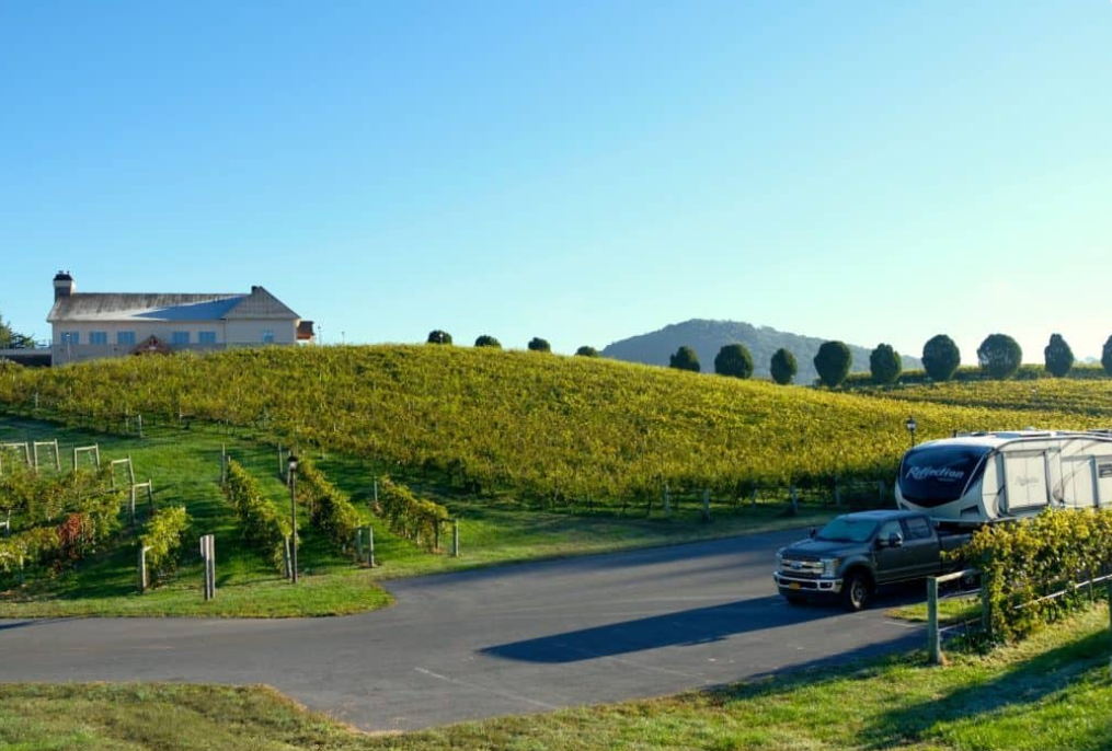 A truck towing a fifth wheel sits in front of a large property overlooking a vineyard.