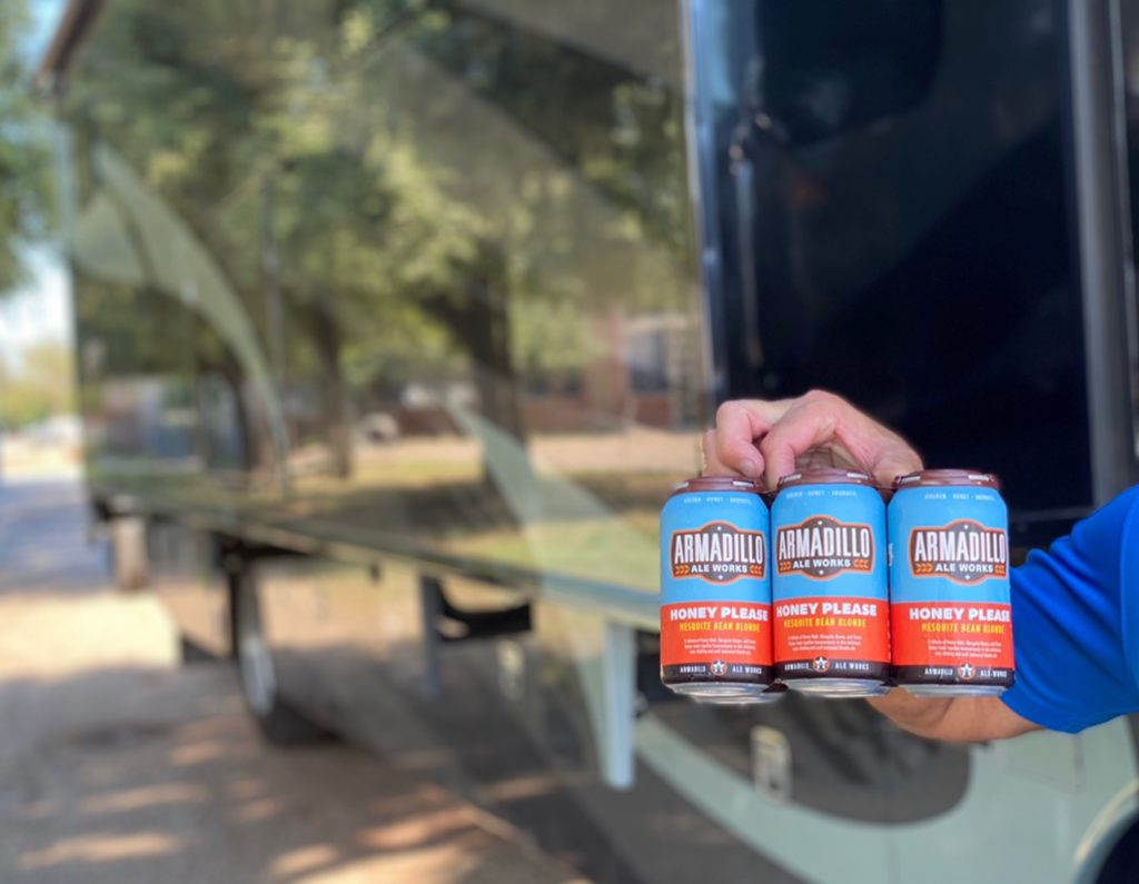 The branding package for Armadillo Ale Works is crisp and clean. The photo shows someone holding a nicely designed 6-pack.
