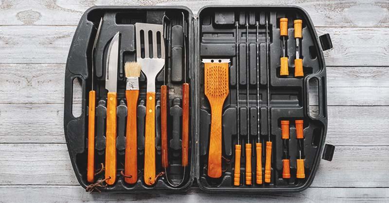 Essential grilling tools like a spatula, basting brush, skewers, knife, etc