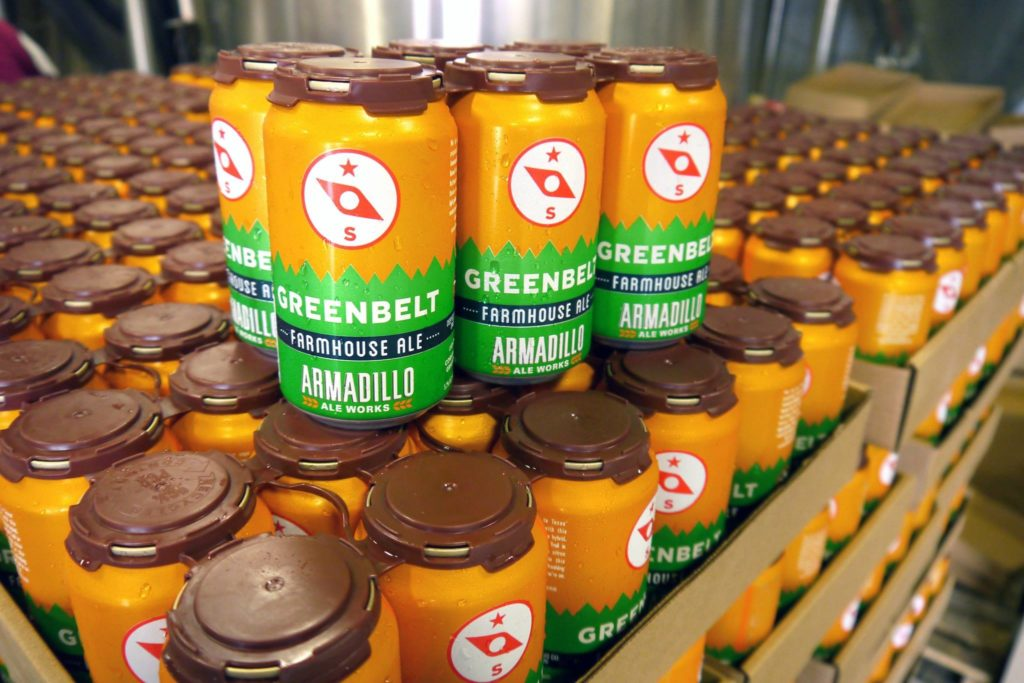 Several stacks of six-packs sit on top of each other, each branded with a golden, brown and green design.