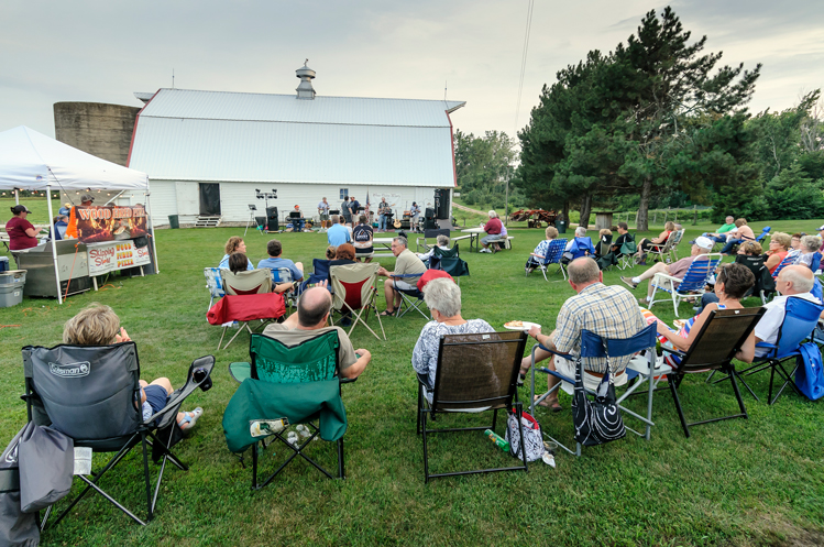 An event takes place on the lawn outside of a winery's tasting room.