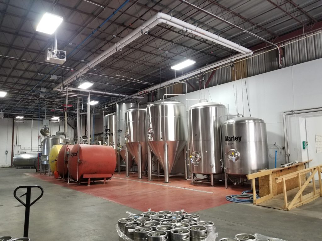 The brewery room is filed with several large, chrome vats, presumably filled with a variety of brews.