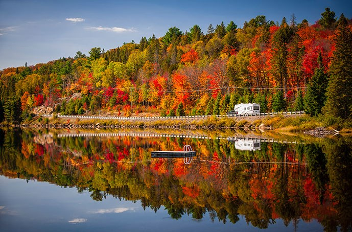 An RV sits beside a lake in front of a back drop of colorful fall trees. The images of the trees and of the RV are mirrored in the lake's water.