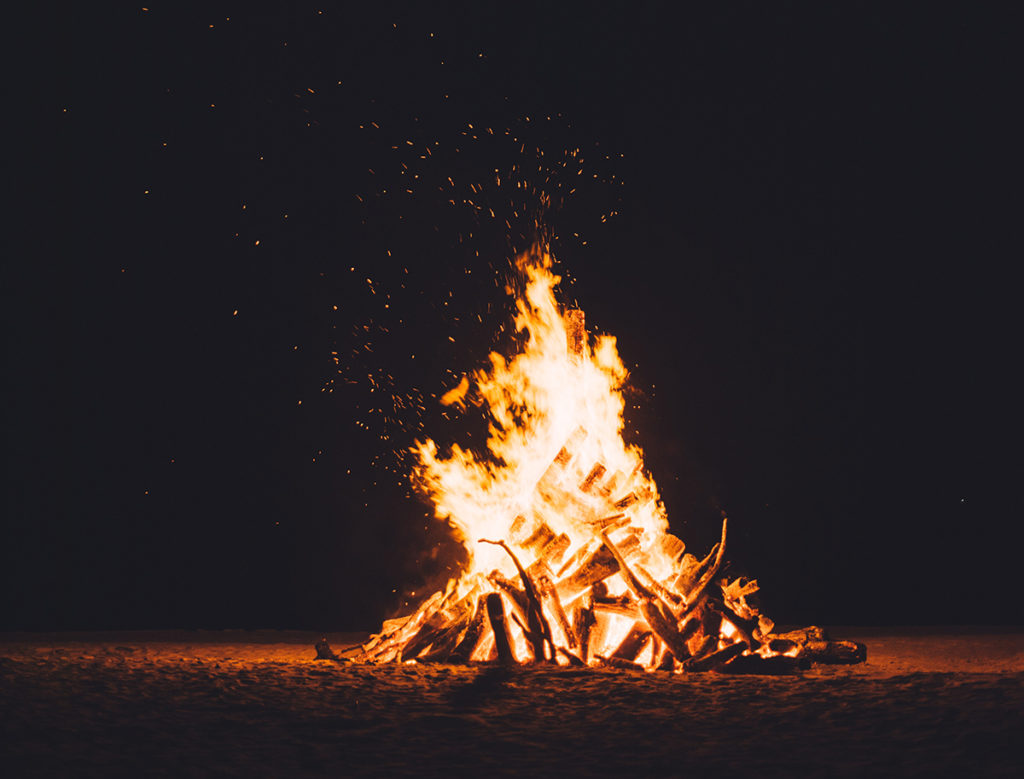 A beautiful bonfire sits beneath a starry sky on a chilly fall night.