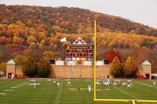 Students play a football game on a large field with a backdrop of fall foliage.
