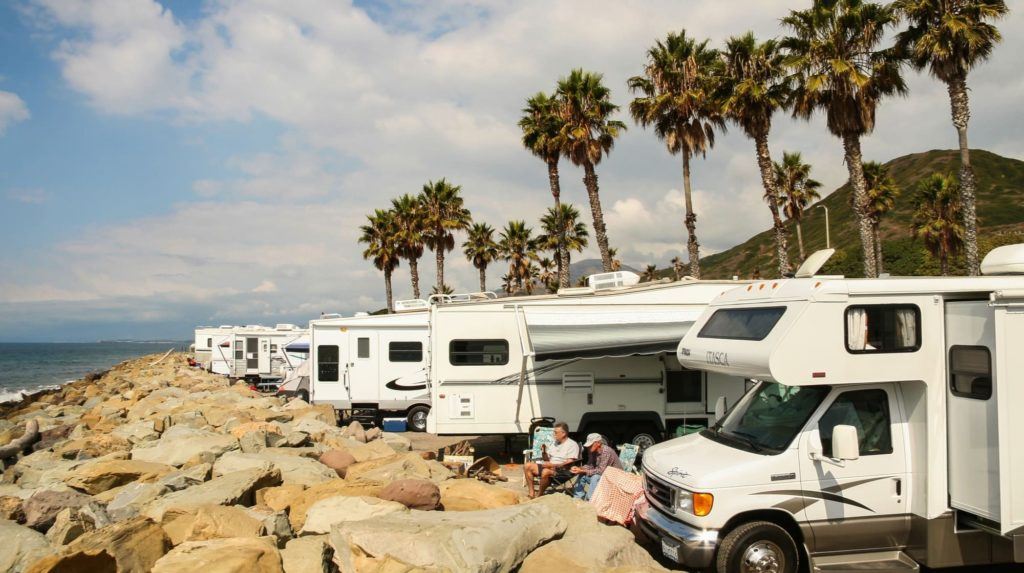 A row of RVs sits parked in front of a beachfront vista during snowbird season.
