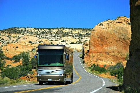 class a motorhome driving down a desert highway. There are buttes, cacti, and hills surrounding it.
