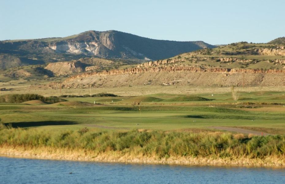 A far-away view of a few holes of a golf course. In the foreground there is a lake and the background is mountains