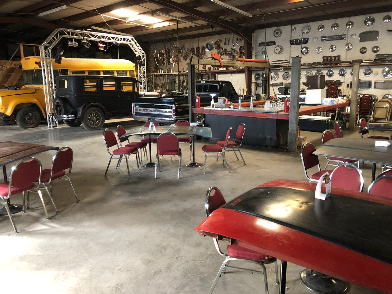 Tables set up in a garage for indoor/outdoor seating at a brewery