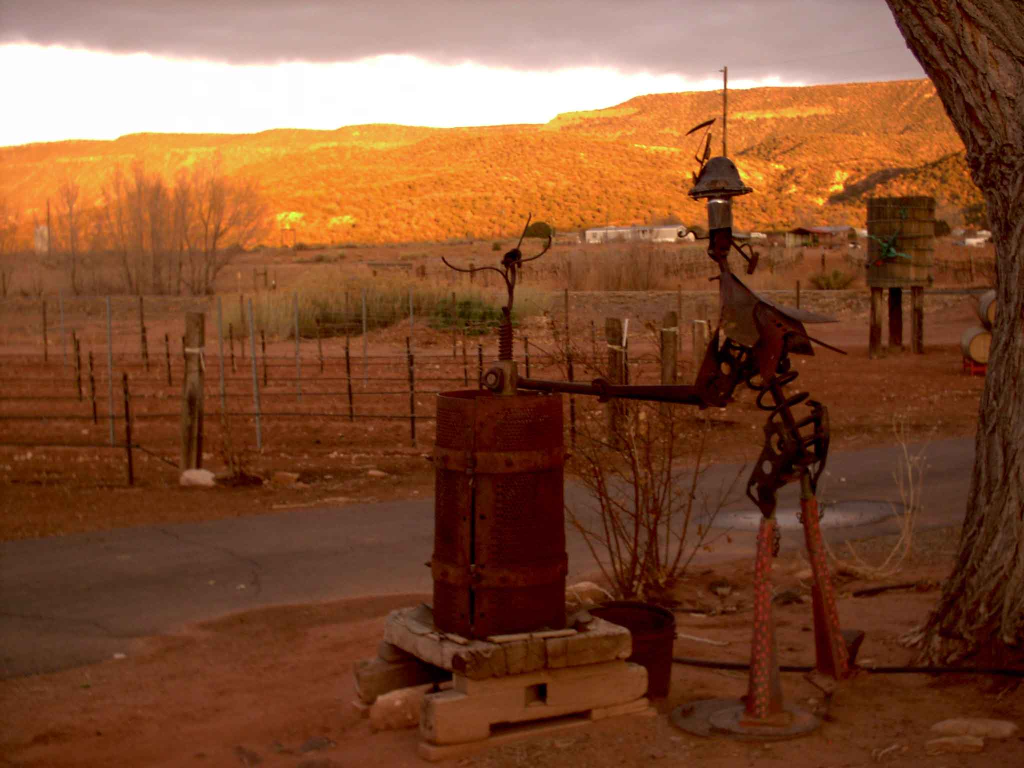 A metal sculpture in the foreground with a sunset in the background