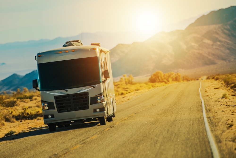 A motorhome driving down the highway with the glare of the sun and mountains in the background