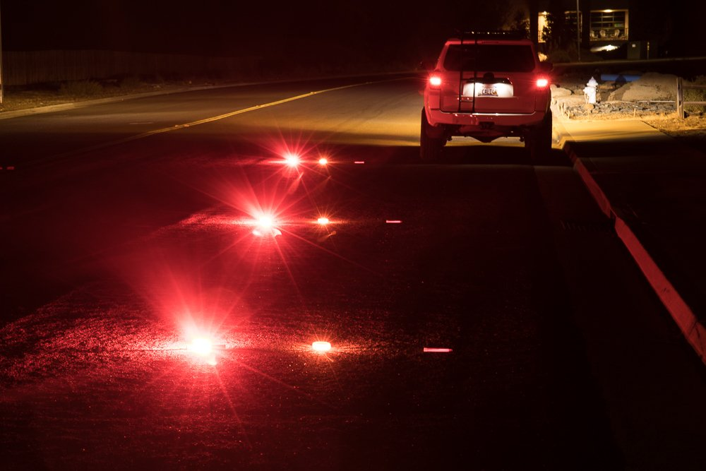 A car is pulled over to the side of the road with flares set up behind it