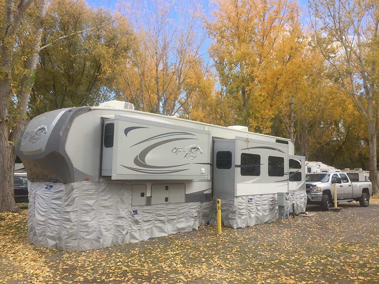 A fifth wheel RV stationary at an RV park in the fall. There is insulated skirting wrapped around the entire bottom of the trailer to help prevent frozen pipes.