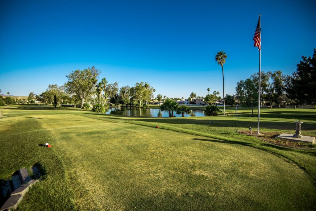 Lush, green, pristine golf course view. The sky is vibrant blue and there is an American flag blowing in the breeze.