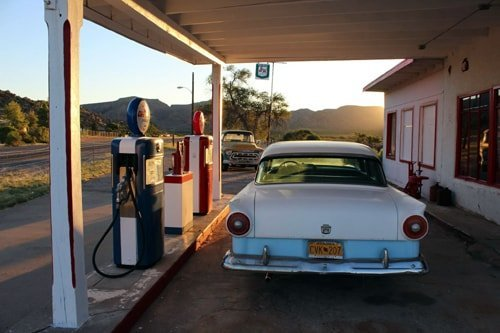 A 1950's style car parked next to retro gas pumps