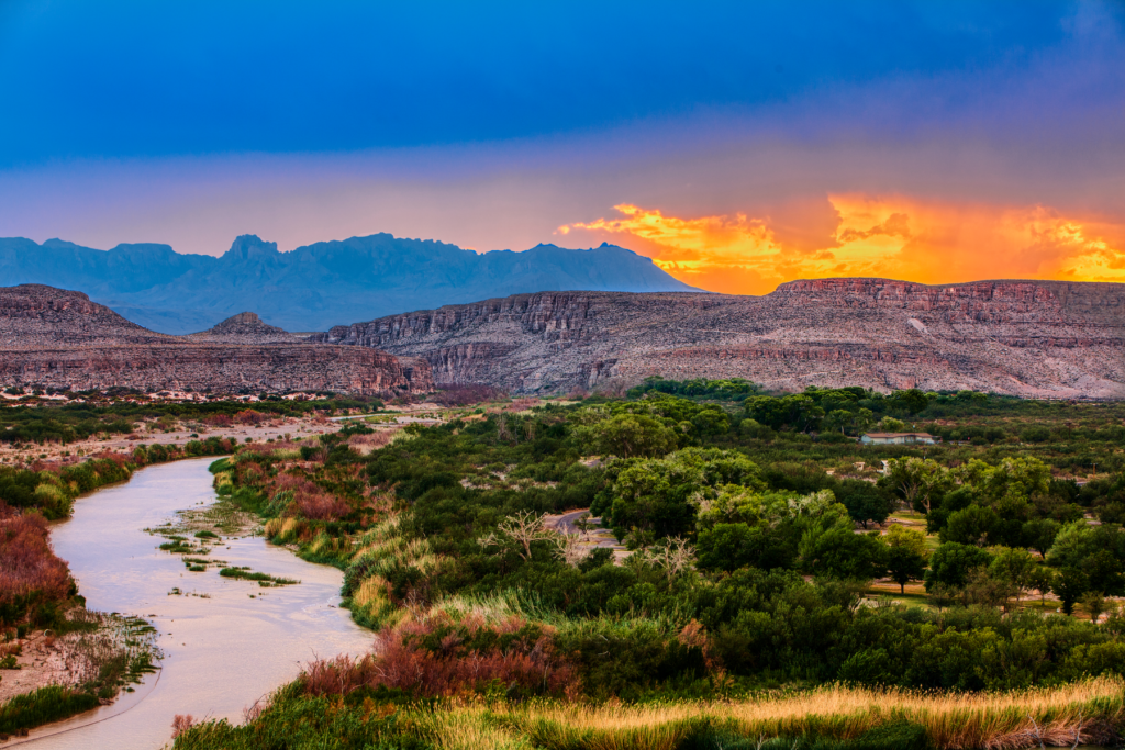 a stunning scenic view of big bend national park. The sun is setting, there is a river running through the shot, and there is lush greenery.