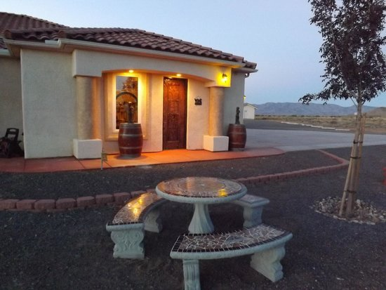 A dusk view of the front of the winery. The structure is white stucco with a red clay roof.