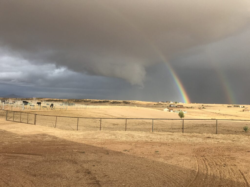 A double rainbow contrasted against the desert farm lands