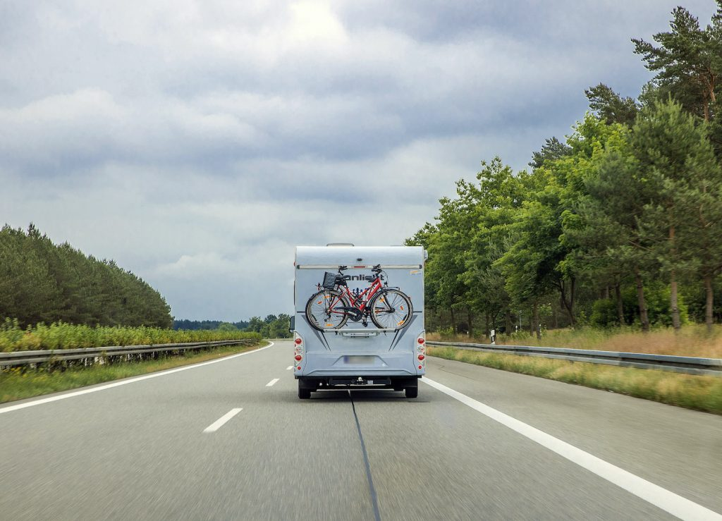 A class C RV driving down the road. Only the back of the RV is visible. There is a red bike mounted o the back.